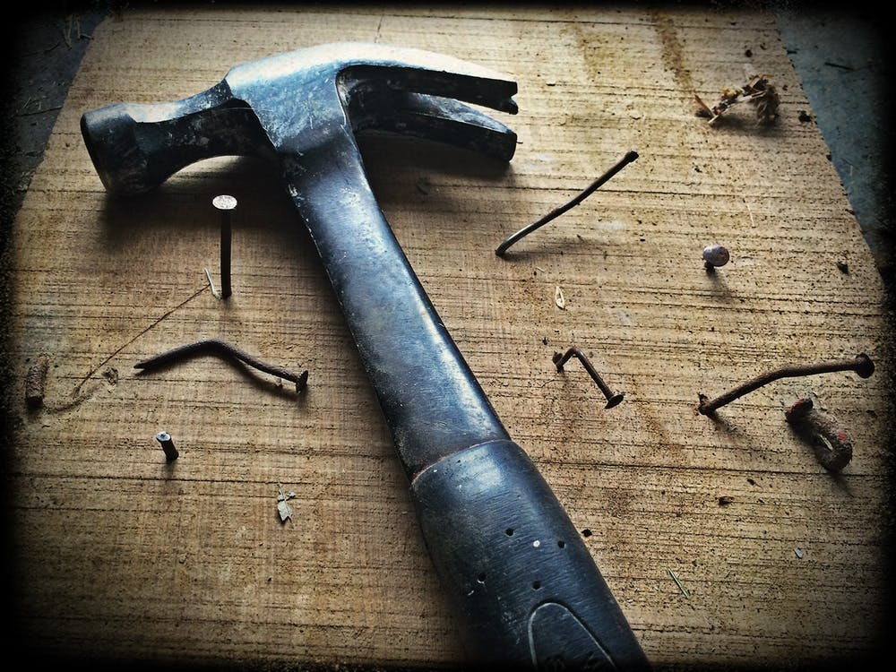 hammer laying on a table with nails